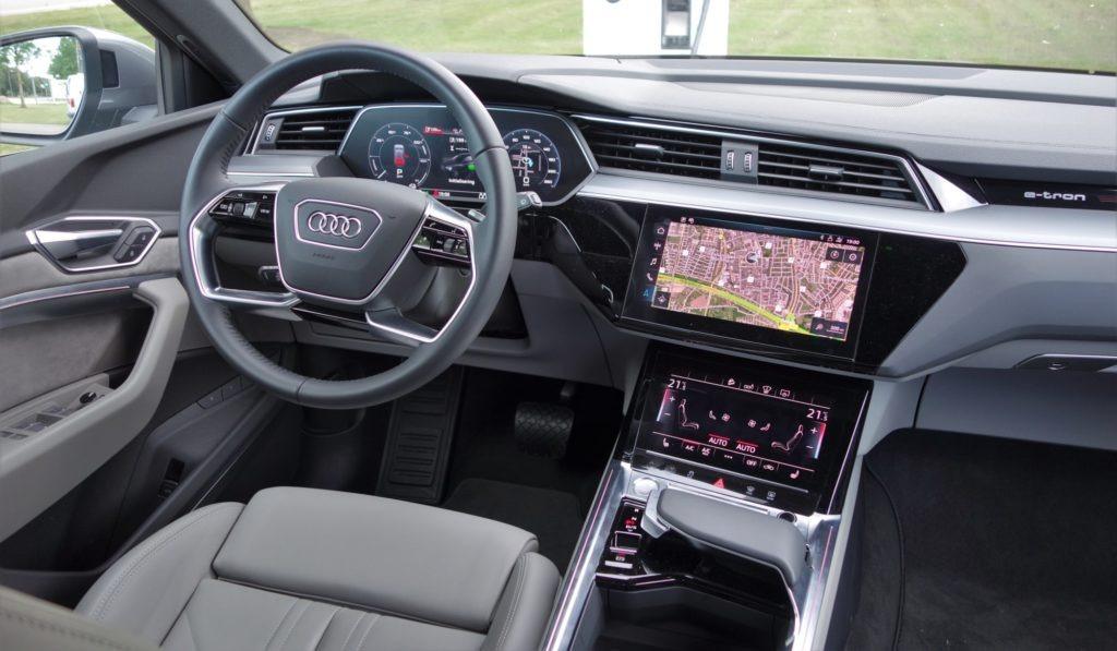 Der er hele 3 skærme i en e-tron; selve instrumentpanelet bag rattet og to yderligere i konsollen. Det fungerer godt. Bemærk håndstøtte og gearvælger nederst til højre i billedet.