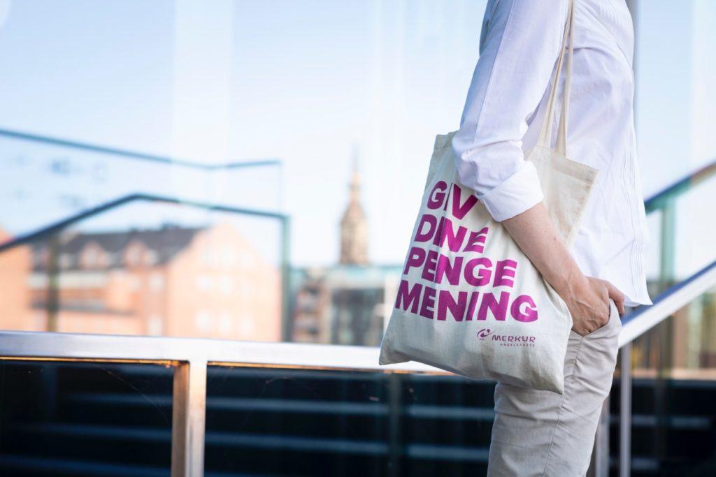 Merkur Andelskasse billede af mulepose med slagordet: Giv dine penge mening